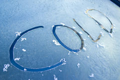 Word cold written on frosty windscreen. The word cold written on a frosted car windscreen and reflecting the blue sky at sunrise Royalty Free Stock Photo