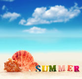 Word of color letters on summer beach and seashell Royalty Free Stock Photos