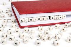 Word Comfortstreek in houten blokken in rood notitieboekje op wh wordt geschreven die Stock Afbeeldingen