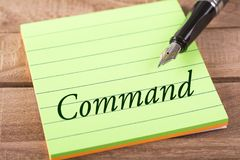 The word command. Written in stick memo with fountain pen on wood Stock Photo