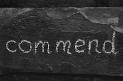 The word commend written with chalk on black stone. Stock Photography