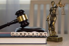 Free Word COMPLAINT Composed Of Wooden Dices. Wooden Gavel And Statue Of Themis In The Background Stock Photo - 153455400