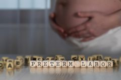Word composed of wooden letters. Pregnant woman in the background royalty free stock photos