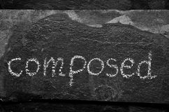 The word COMPOSED written with chalk on black stone. Stock Photo
