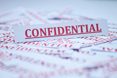 The word Confidential. The word Confidential surrounded by some shredded papers Stock Photos