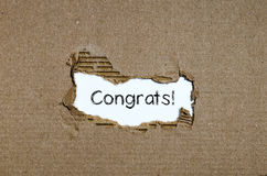 The word congrats appearing behind torn paper. The word congrats appearing behind torn paper royalty free stock photography