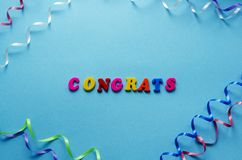 Word `congrats` from magnetic letters and serpentine on blue pap. Er background Royalty Free Stock Images