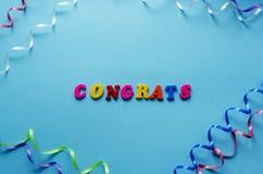 Word ` congrats ` van magnetische brieven en kronkelweg op blauwe pap Royalty-vrije Stock Afbeeldingen