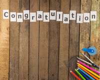 Word congratulation  and stationery set  on wooden Royalty Free Stock Photo