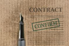 Word Contract and a pen. Word Contract written on vintage background and a fountain pen Royalty Free Stock Image