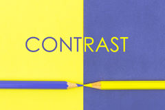 Word CONTRAST written over Yellow and Violet coloured paper Royalty Free Stock Photos