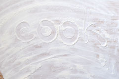 Word cook on wood board with flour Royalty Free Stock Photos