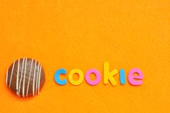 The word cookie with a chocolate covered shortbread cookie. On an orange background royalty free stock photo