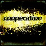 Word `cooperation` on black and yellow grunge background. Communication concept. Royalty Free Stock Image