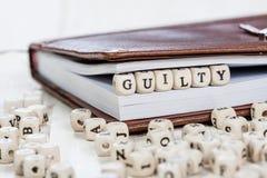 Word COUPABLE sur la vieille table en bois Images stock