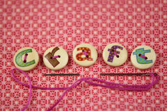 The word craft spelled in hand painted letters on buttons. On a vibrant textile background Royalty Free Stock Photos