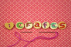 The word crafts spelled in hand painted letters on buttons. On a vibrant textile background Stock Photos