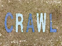 The word CRAWL on the floor in a kids park. The word CRAWL stencilled in navy and baby blue letters onto the floor made out of wet pour rubber surface material stock photo