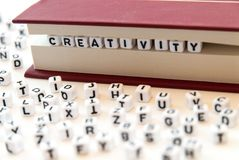 Word creativity written with letters between a book pages white background with letters spread around education reading concept. Photo stock photos