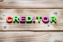 Word creditor. On wooden background. Business theme Stock Photography