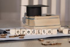 Word CREDITS composed of wooden dices. Black graduate hat and books in the background. Closeup stock photos