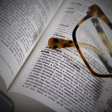 Word crisis in dictionary and brown glasses on it. Dictionary page closeup with the word crisis and brown glasses on it Royalty Free Stock Images