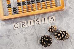 Word CRISIS laid out of handwritten letters on cardboard squares near old wooden abacus and three cones. On gray cracked concrete stock photography