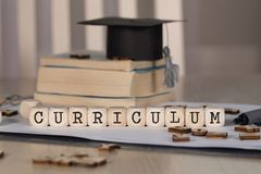 Word CURRICULUM composed of wooden dices. Black graduate hat and books in the background. Closeup stock photo