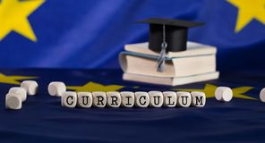 Word CURRICULUM composed of wooden letters. Black graduate hat on EU flag in the background. Closeup stock photography
