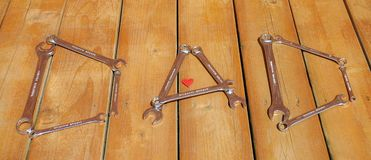Word `DAD` arranged from tools. Father`s Day. Word DAD made from wrenches on wooden background. Small red heart in a letter A royalty free stock photos