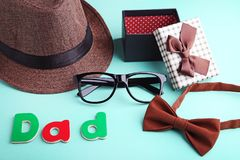 Word Dad with bow tie, glasses, hat. And gift box on mint background Stock Photos