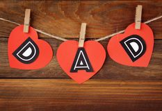 Word DAD made of paper hearts as greeting. For Father's day on string against wooden background Stock Images