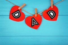 Word DAD made of paper hearts as greeting. For Father's day on string against wooden background Stock Photo