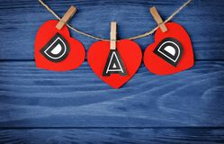 Word DAD made of paper hearts as greeting. For Father's day on string against wooden background Stock Photos