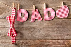 Word DAD made of paper letters and bow tie hanging. On rope against wooden background Stock Photography