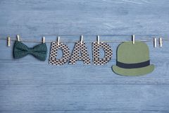 Word DAD made of paper letters hanging. On rope against wooden background Stock Photography