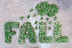 Word DALING die van droog groen gras met wolk en regendruppels op grijze steenachtergrond wordt gemaakt Regenachtig weer bij de h Stock Foto
