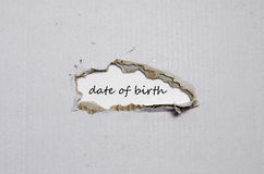 The word date of birth appearing behind torn paper Royalty Free Stock Images