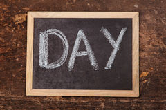 Word day handwritten on a chalkboard. On wooden background Royalty Free Stock Image
