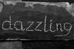 The word dazzling written with chalk on black stone. Stock Photo