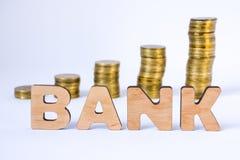 Word de bank van driedimensionele brieven is in voorgrond met de groeikolommen van muntstukken op vage achtergrond Bankconcept vo stock foto's