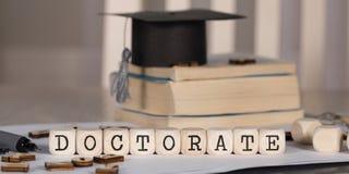 Word de DOCTORAATSTITEL uit houten wordt samengesteld die dobbelt stock fotografie