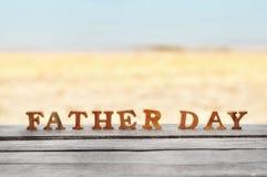 Word de fête des pères en bois sur le bois sur l'idée de fond de plage Photographie stock libre de droits