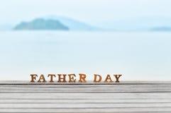 Word de fête des pères en bois sur le bois sur l'idée de fond de plage Image libre de droits