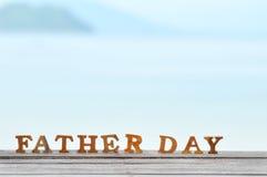 Word de fête des pères en bois sur le bois sur l'idée de fond de vue de mer Photographie stock libre de droits