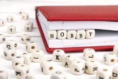 Word de Hobby in houten blokken in rood notitieboekje op wit wordt geschreven dat streeft na Stock Foto
