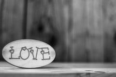 Word de l'amour en noir et blanc sur un fond en bois Image stock