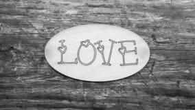Word de l'amour en noir et blanc sur un fond en bois Images stock
