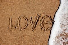 Word de liefde op het strand wordt gewassen weg met water Royalty-vrije Stock Foto's