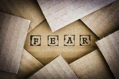 Word de Vrees maakt door zwarte alfabetzegels op karton stock foto